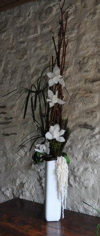 Vase blanc pour orchidées cymbidium blancs mis en valeur par un beau contraste avec le bois brut du polygonome