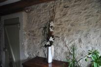 Création florale haute de 1 m environ en technique d'auto calage avec du bois de polygonome. Les orchidéess blanches sont misent en valeur pas le contraste de l'allure brut et naturel du boi.