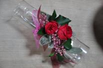 Un tube transparent où sont lovées des fleurs stabilisées: Roses de jardin stabilisées, lierre et feuille d'oreille d'ours stabilisées, poivre rose et ruban assortis