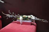 Un contenant argenté relevé d'une ceinture de diament, accueille ecorces de fougère arborescente, rose blanc crème, amarante, eucalyptus, et travail de feuille de lierre avec des perles