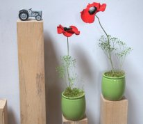 2 coquelicots en pétales rouges stabilisées sont posés sur des colonnes de bois à coté d'un tracteur et discutent.