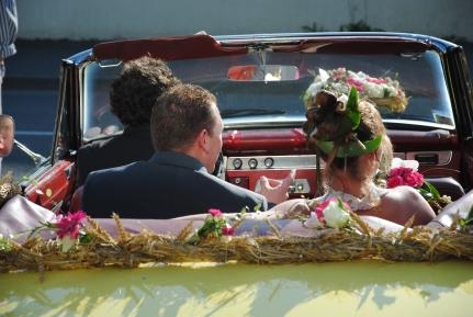 """Une guirlande de paille et de fleurs sur la voiture des mariés pour """"coller"""" au thème """"Paille"""" du mariage."""