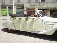 Des cônes fleuris donnent un élégance contemporaine sur cette voiture de collection blanche. Les cônes peuvent être réutilisés pour la décoration de la salle.
